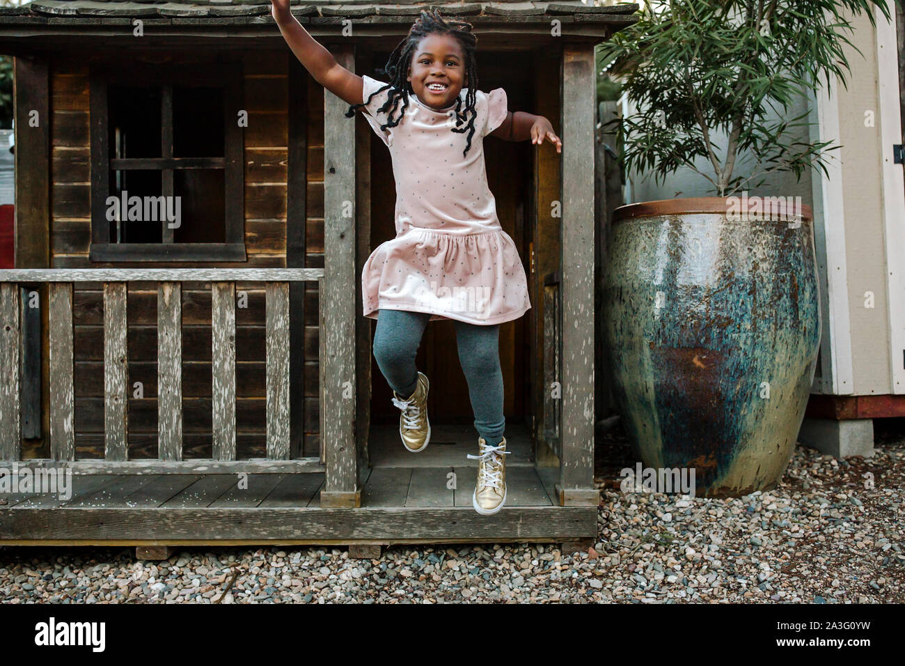 Laughing young black girl with long braids jumping from cabin porch Stock Photo