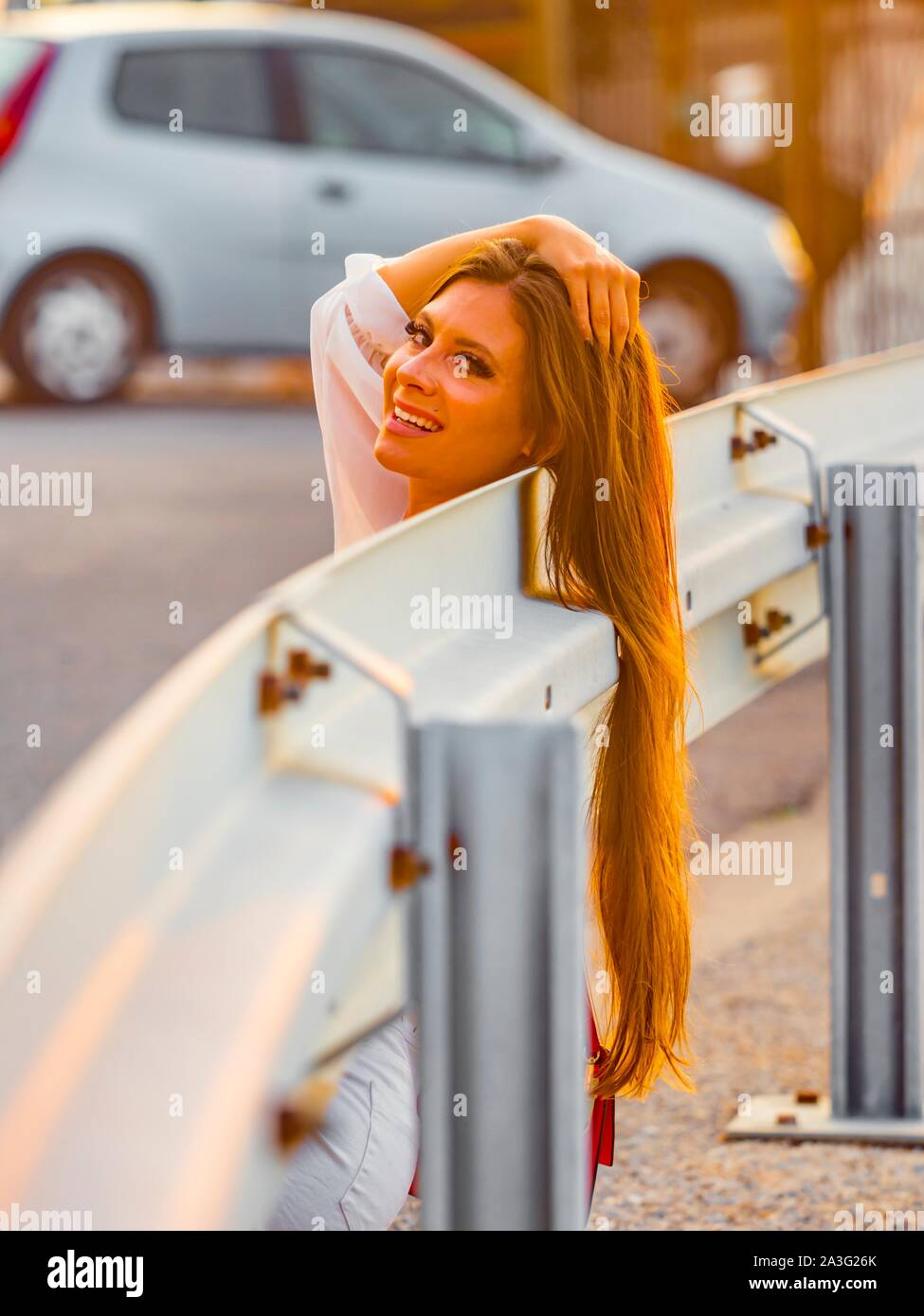 Smiling attractive young woman against sunset light smiling at camera eyeshot long hair on metal road fence hand holding hair above head Stock Photo