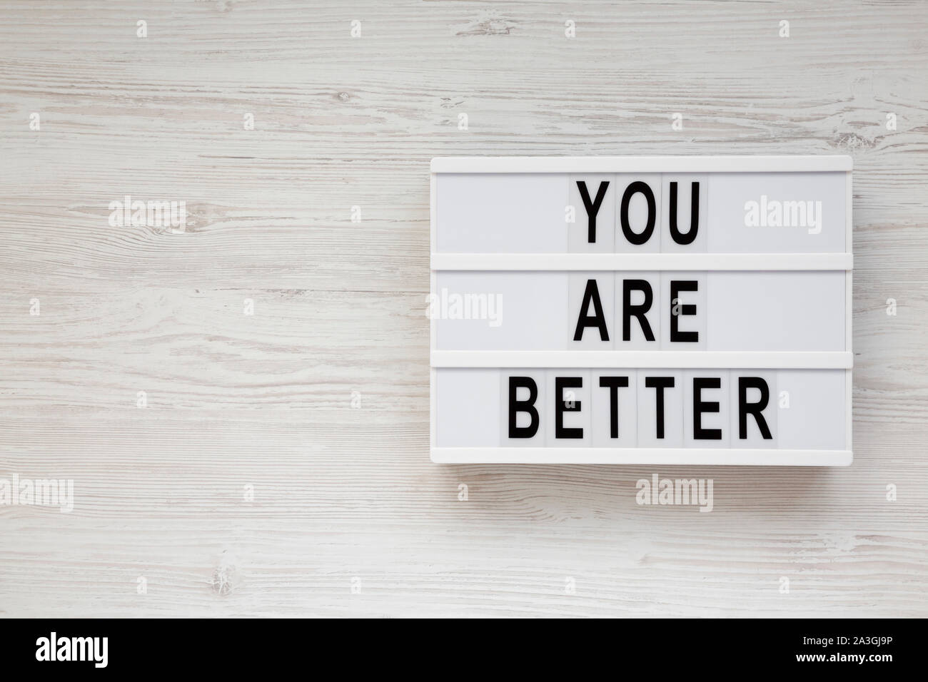 'You are better' words on a lightbox on a white wooden background, top view. Overhead, from above. Flat lay. Copy space. Stock Photo
