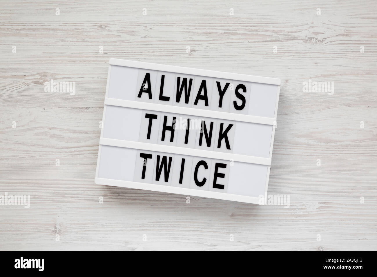 'Always think twice' words on a modern board over white wooden surface, top view. Overhead, from above. Flat lay. Stock Photo