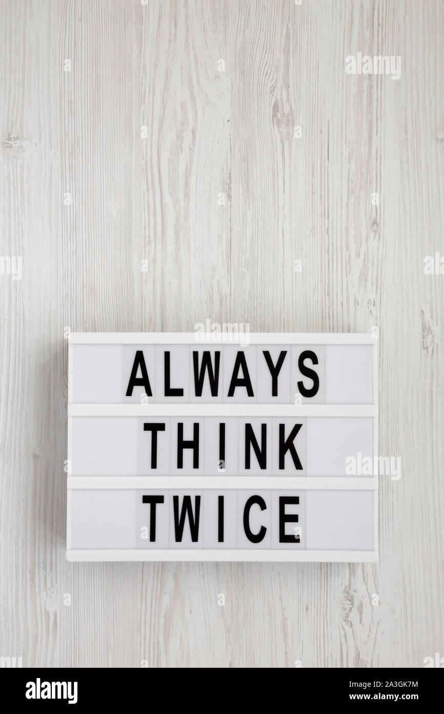 'Always think twice' words on a lightbox on a white wooden background, top view. Overhead, from above, flat lay. Space for text. Stock Photo
