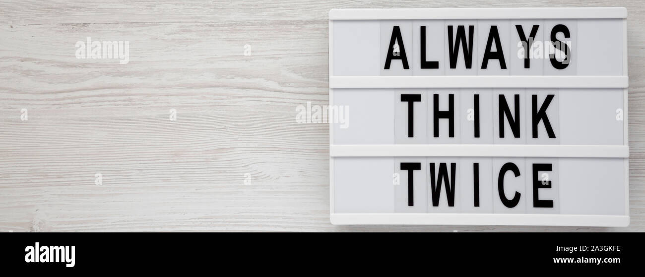 'Always think twice' words on a lightbox on a white wooden surface, top view. Overhead, from above, flat lay. Copy space. Stock Photo