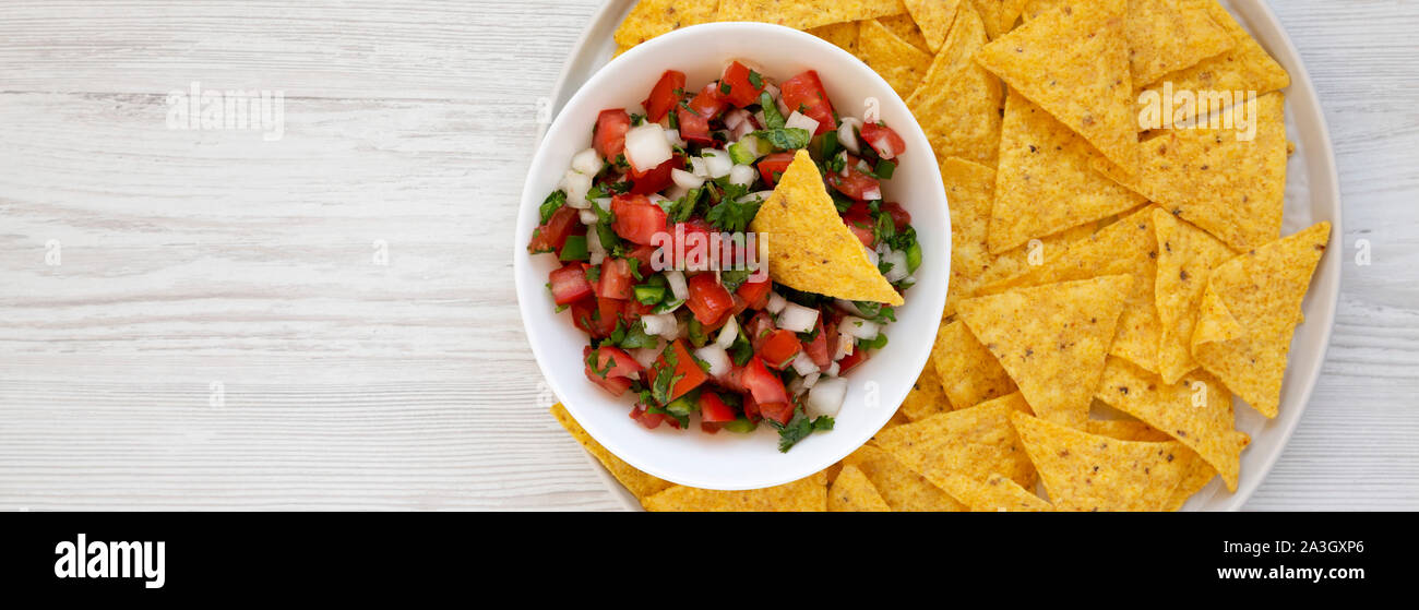 Pico de Gallo with gluten free tortilla chips on a white wooden background, top view. Flat lay, overhead, from above. Space for text. Stock Photo
