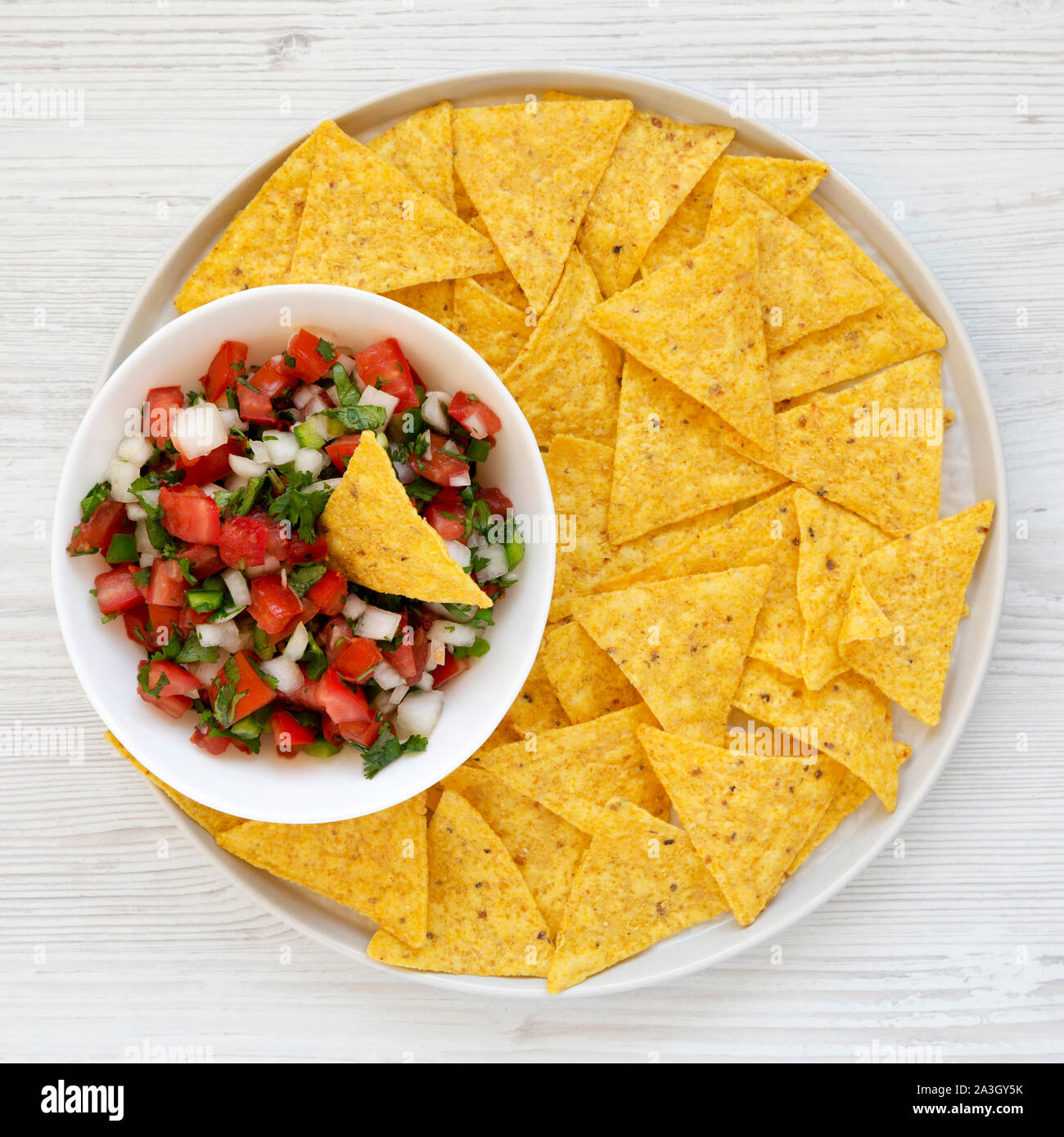 Pico de Gallo with gluten free tortilla chips on a white wooden surface, top view. Flat lay, overhead, from above. Close-up. Stock Photo