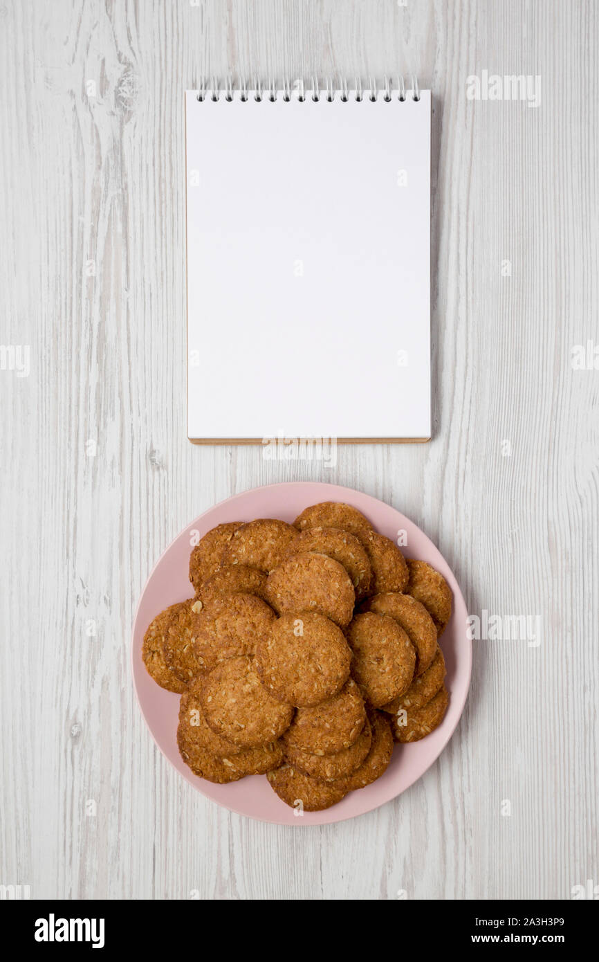 Cereal cookies on a pink plate, blank notepad on a white wooden surface, overhead view. Flat lay, top view, from above. Space for text. Stock Photo