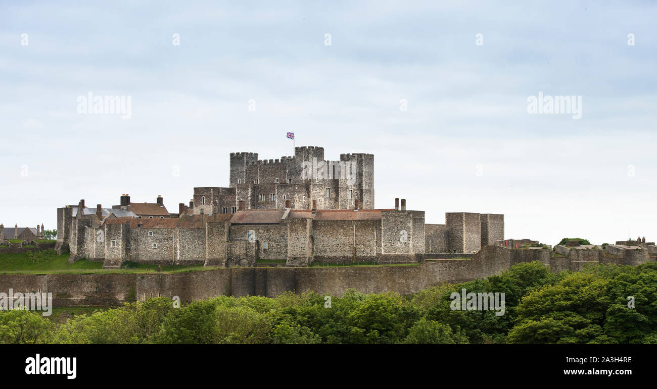 Dover Castle,postcard view, Union Jack flying from keep. British Heritage. Blue sky. Copy space. Curtain perimeter walls and surrounding greenery. Stock Photo