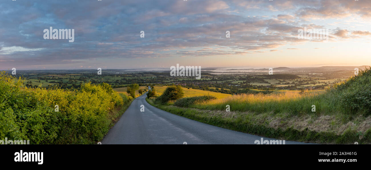 The road to Okeford Fitzpaine; dawn on the longest day in the Blackmore Vale, from Okeford Hill, Dorset, England, UK Stock Photo