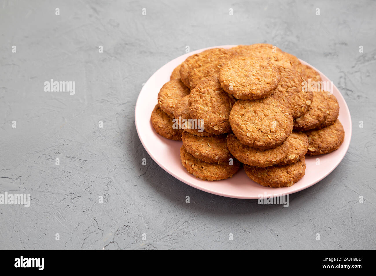 Cereal cookies on a pink plate on a gray surface, side view. Copy space. Stock Photo