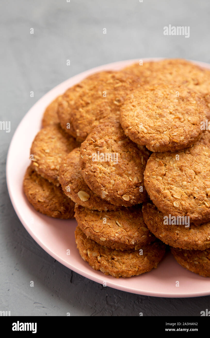 Cereal cookies on a pink plate on a gray surface, low angle view. Close-up. Stock Photo