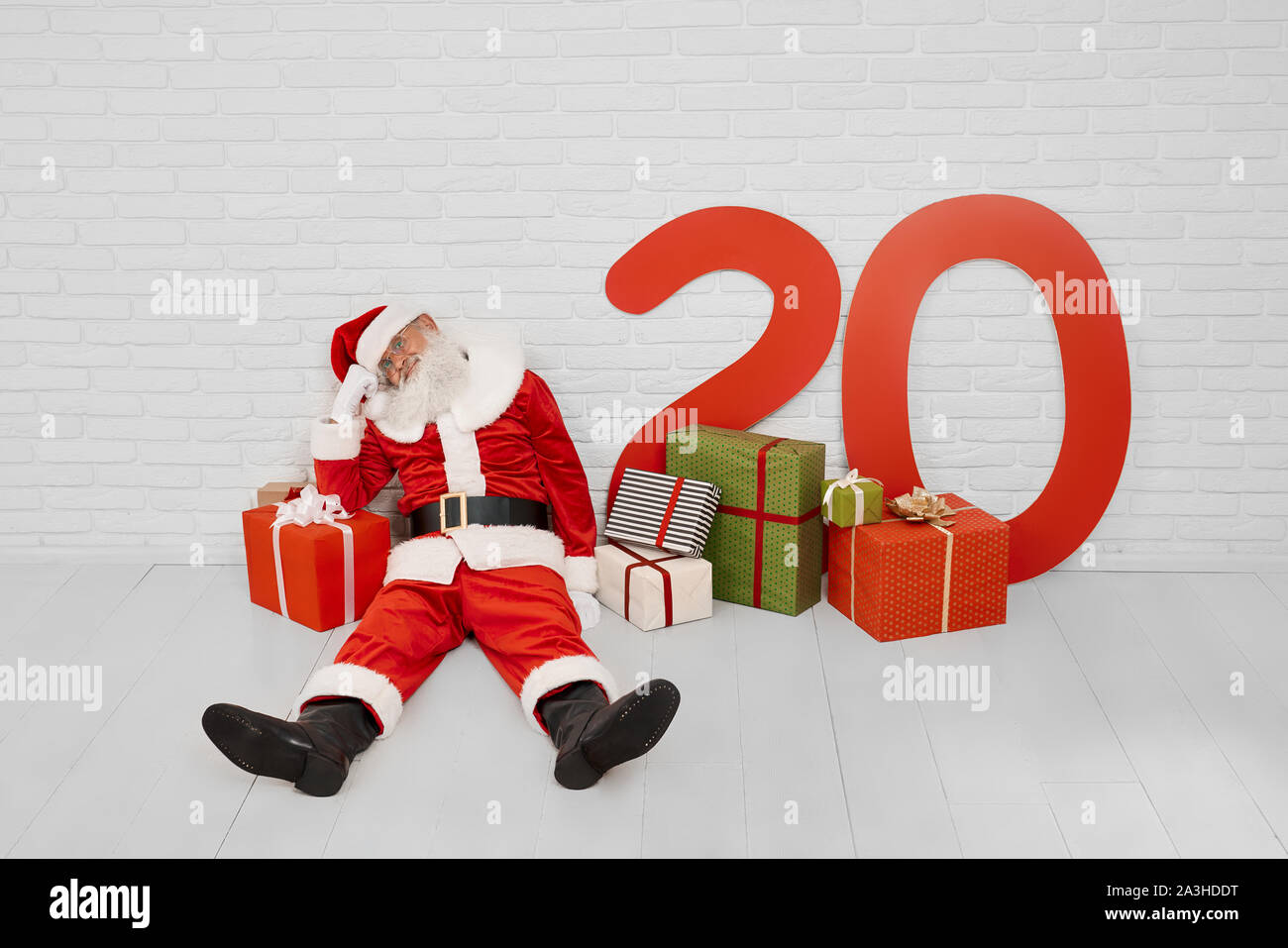 2020 Big Christmas Box Gifts Tired mature Santa Claus sitting on white floor near red big gift