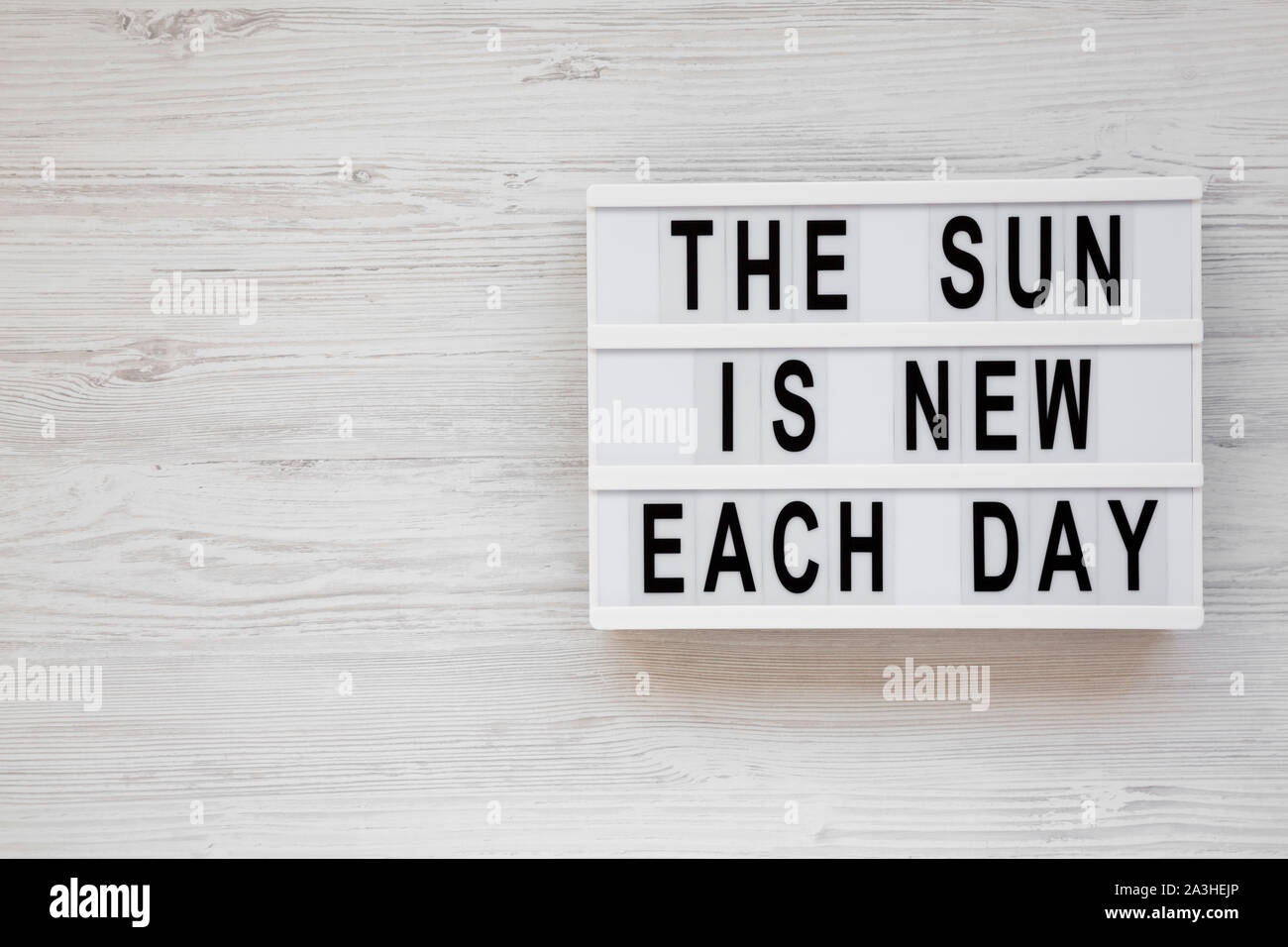'The sun is new each day' words on a lightbox on a white wooden background, top view. Overhead, from above, flat lay. Copy space. Stock Photo
