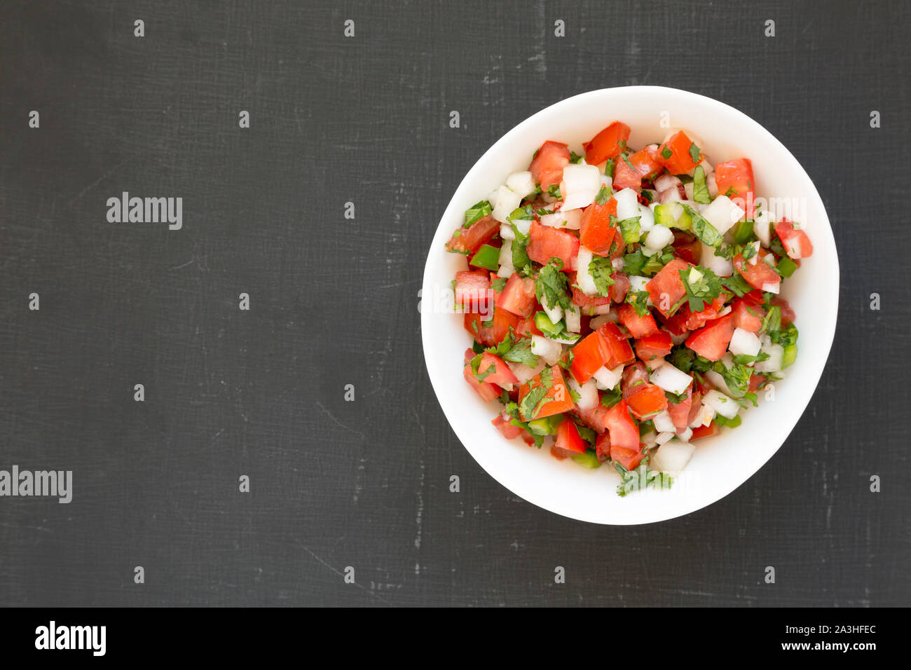 Top view, Pico de Gallo in a white bowl on a black surface. Overhead, from above, flat lay. Space for text. Stock Photo