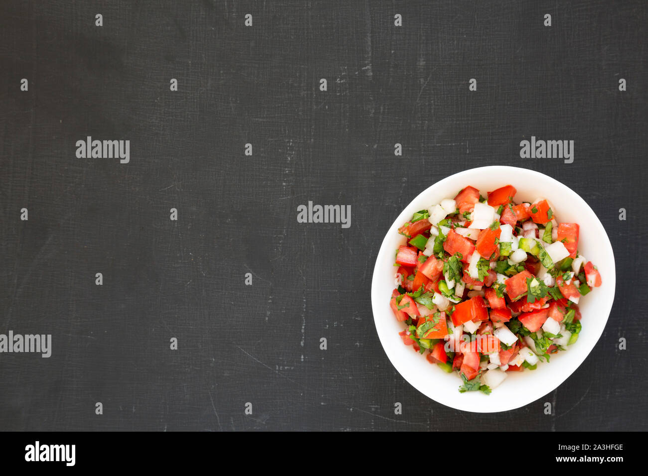 Pico de Gallo in a white bowl on a black surface, top view. Overhead, from above, flat lay. Copy space. Stock Photo