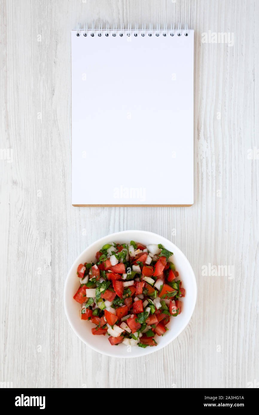 Pico de Gallo in a white bowl, blank notebook on a white wooden background, top view. Overhead, from above, flat lay. Space for text. Stock Photo