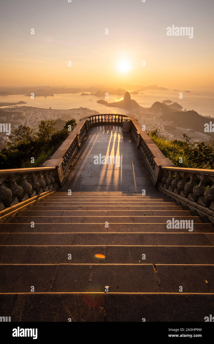 Beautiful sunrise view from an empty Corcovado Mountain staircase to the Sugar Loaf, city and ocean, Rio de Janeiro, Brazil Stock Photo
