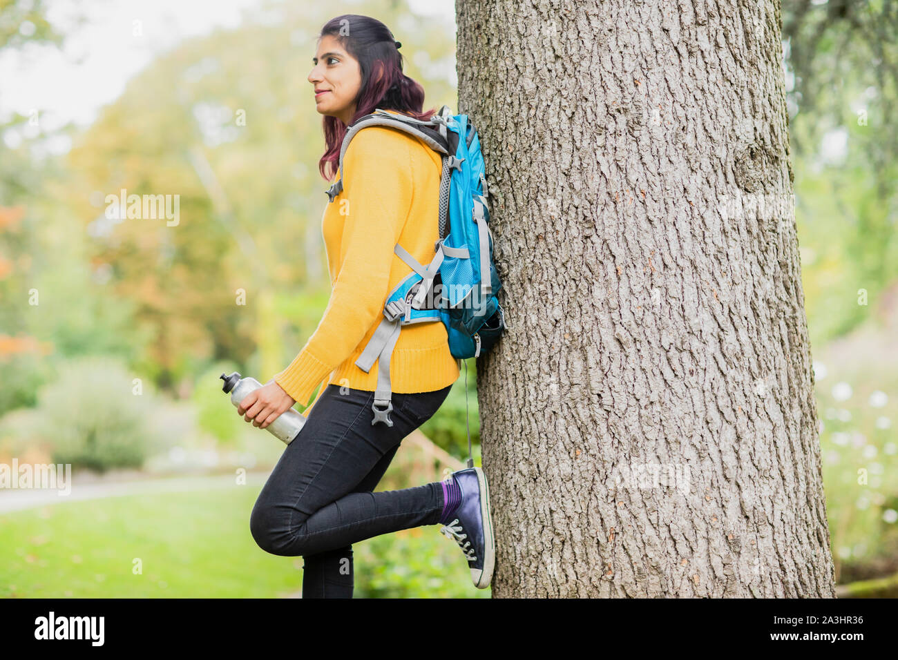 young woman hiking and standing near a tree Stock Photo