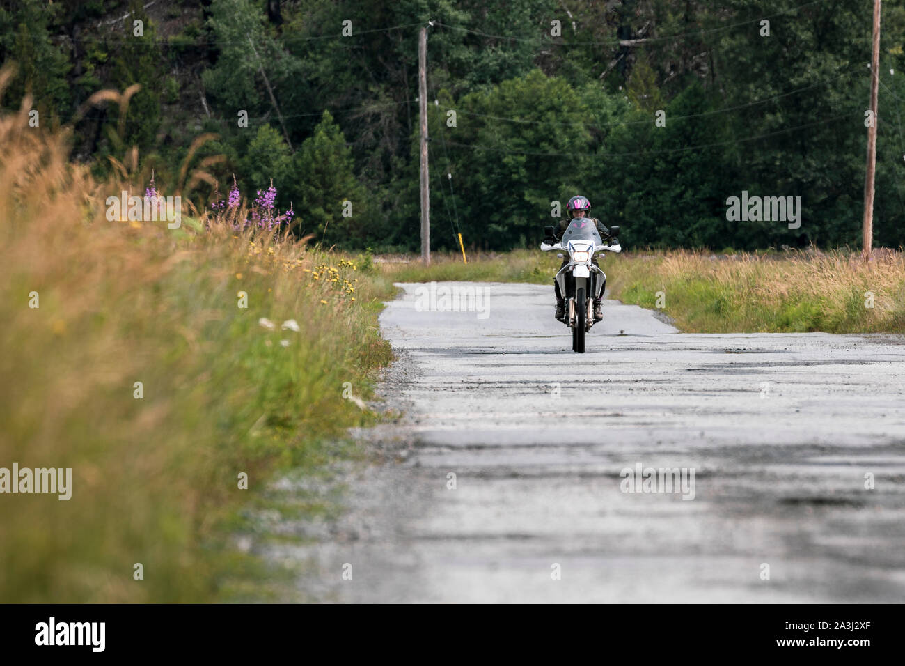 A woman rides her motorcycle on a cloudy summer day. Stock Photo