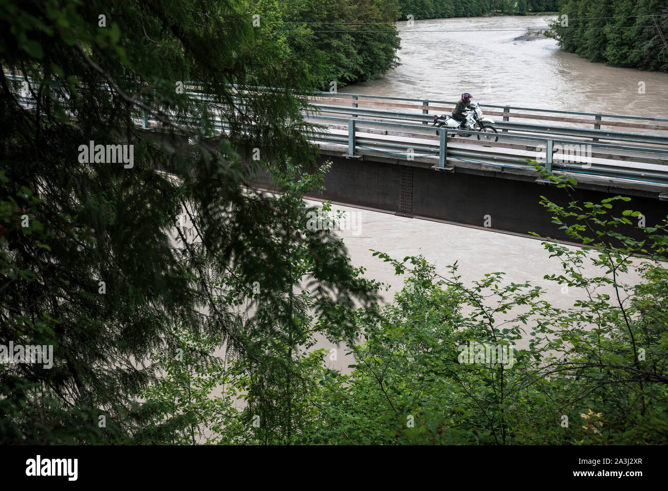A woman rides her motorcycle across a bridge on a cloudy summer day. Stock Photo