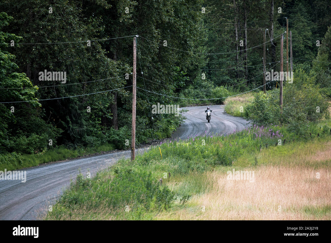 A women rides her motocycle on a gravel road in Canada. Stock Photo
