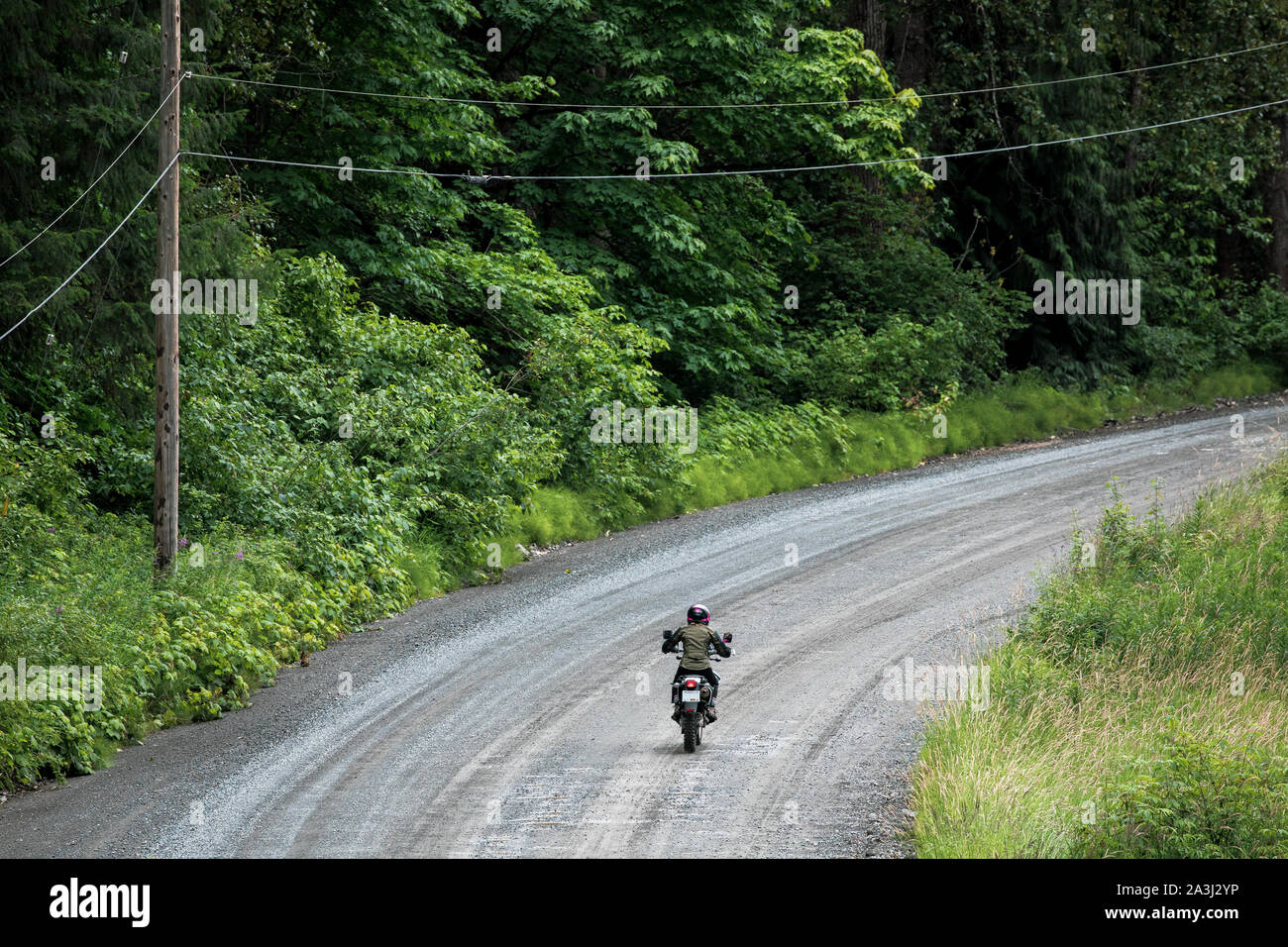 A women rides her motorcycle on a gravel road in Canada. Stock Photo