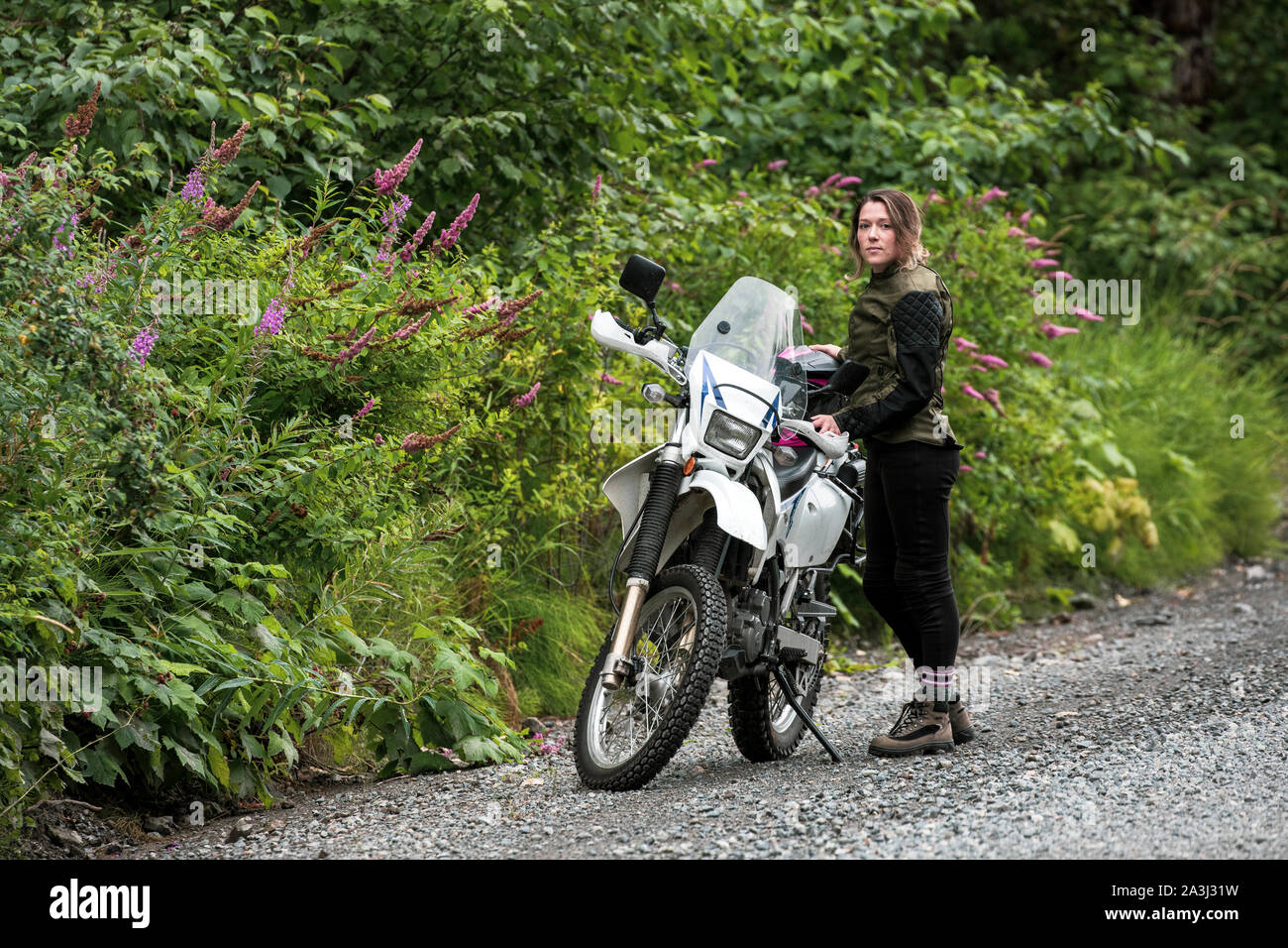 A women takes a break from motorcycle riding and stands with her bike. Stock Photo