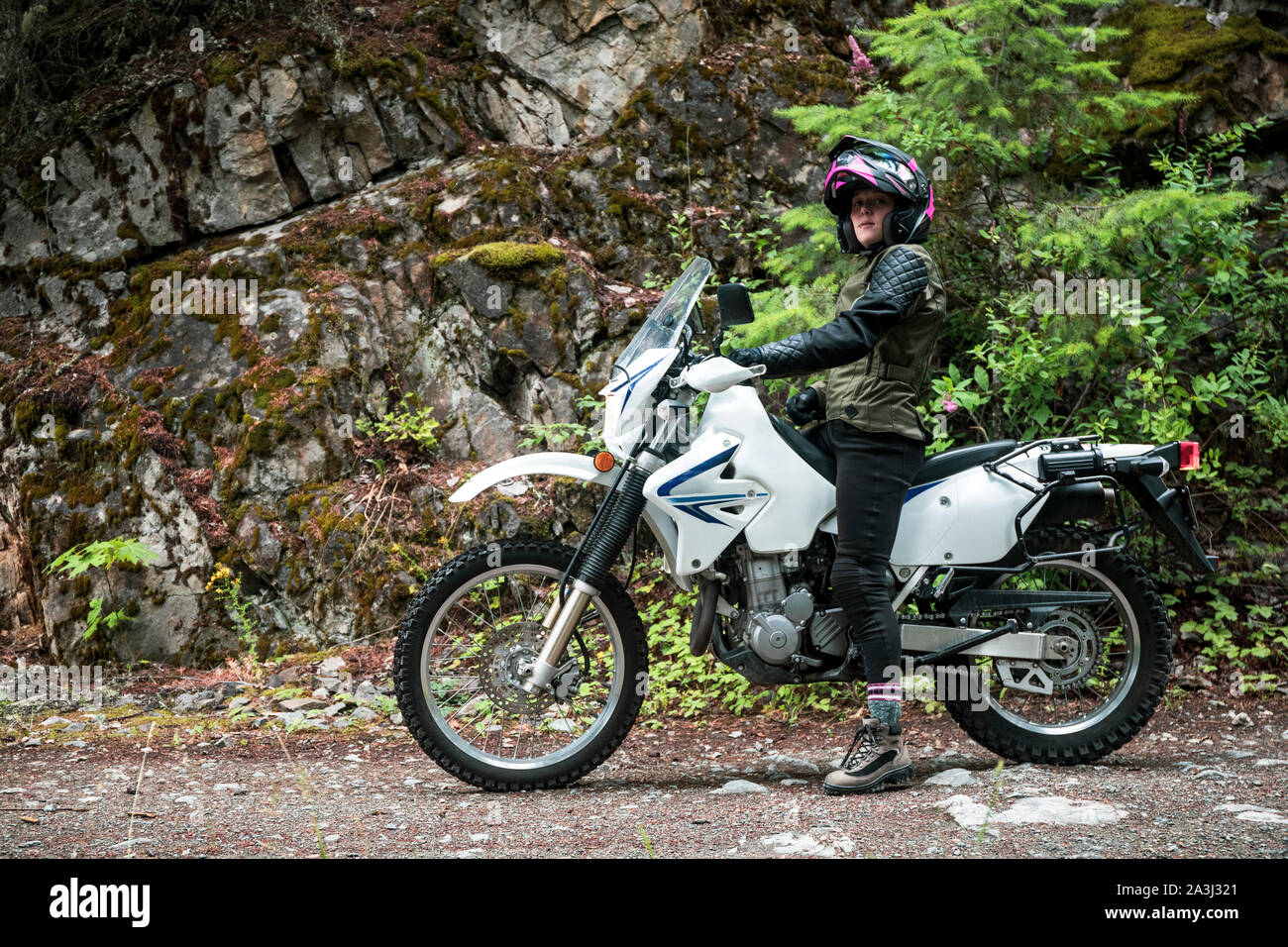 A women riding a motorcycling stops on a gravel road. Stock Photo