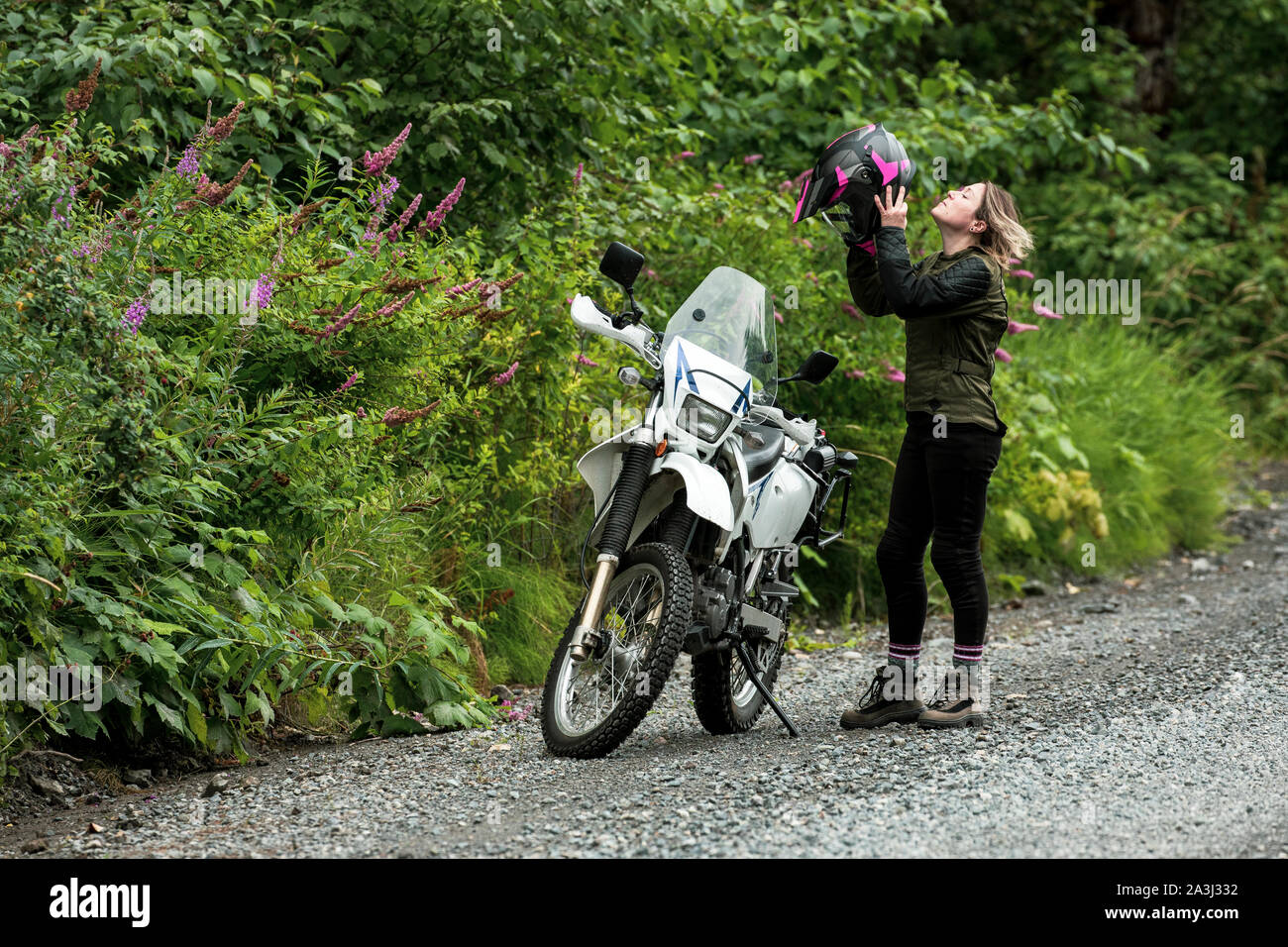 A women takes a break from motorcycle riding and takes off her helmet. Stock Photo