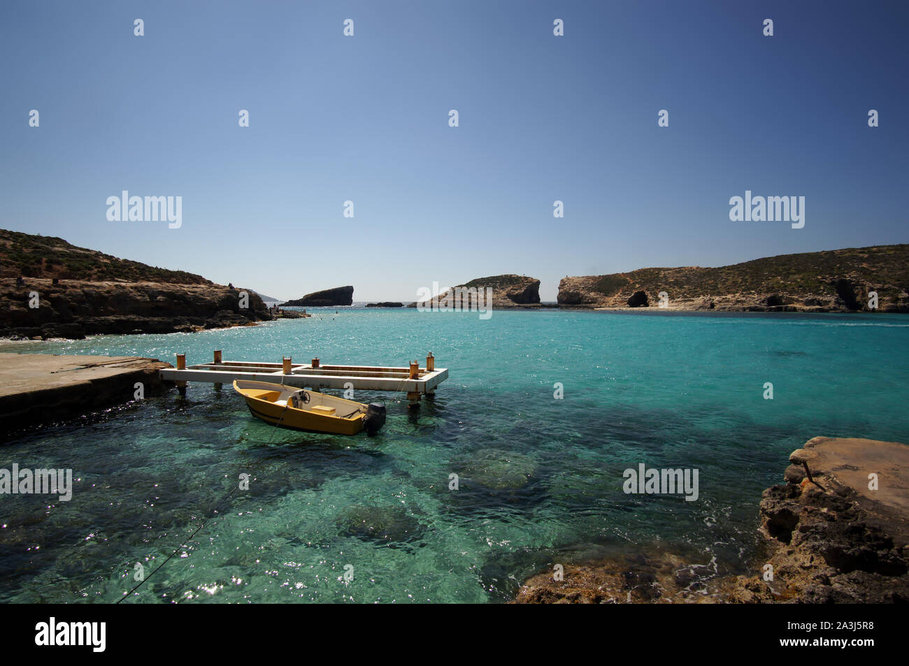 Boat and rocks of Blue Lagoon in Comino, Malta during the winter day Stock Photo