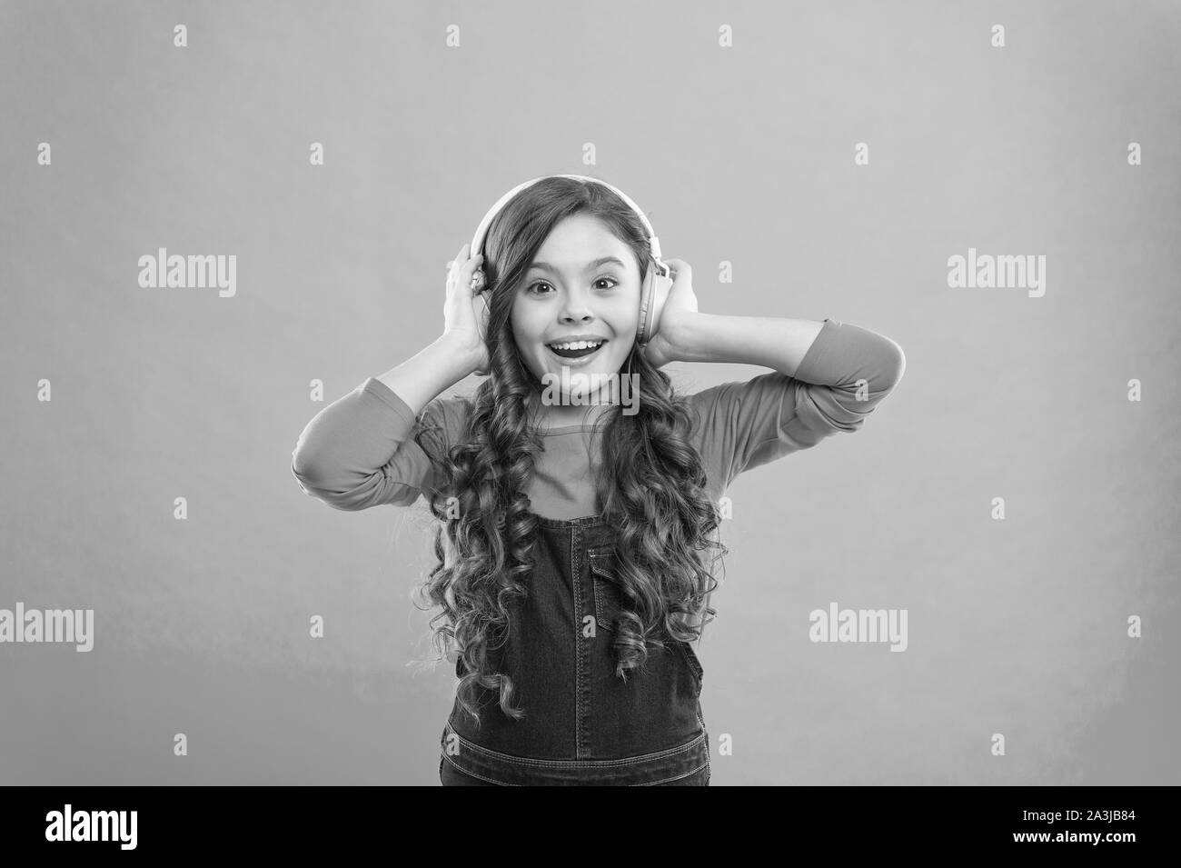 Feeling the beauty of the song. Cute small child listening to song on blue background. Adorable little girl enjoying song playing in headphones. Composing a song. Stock Photo