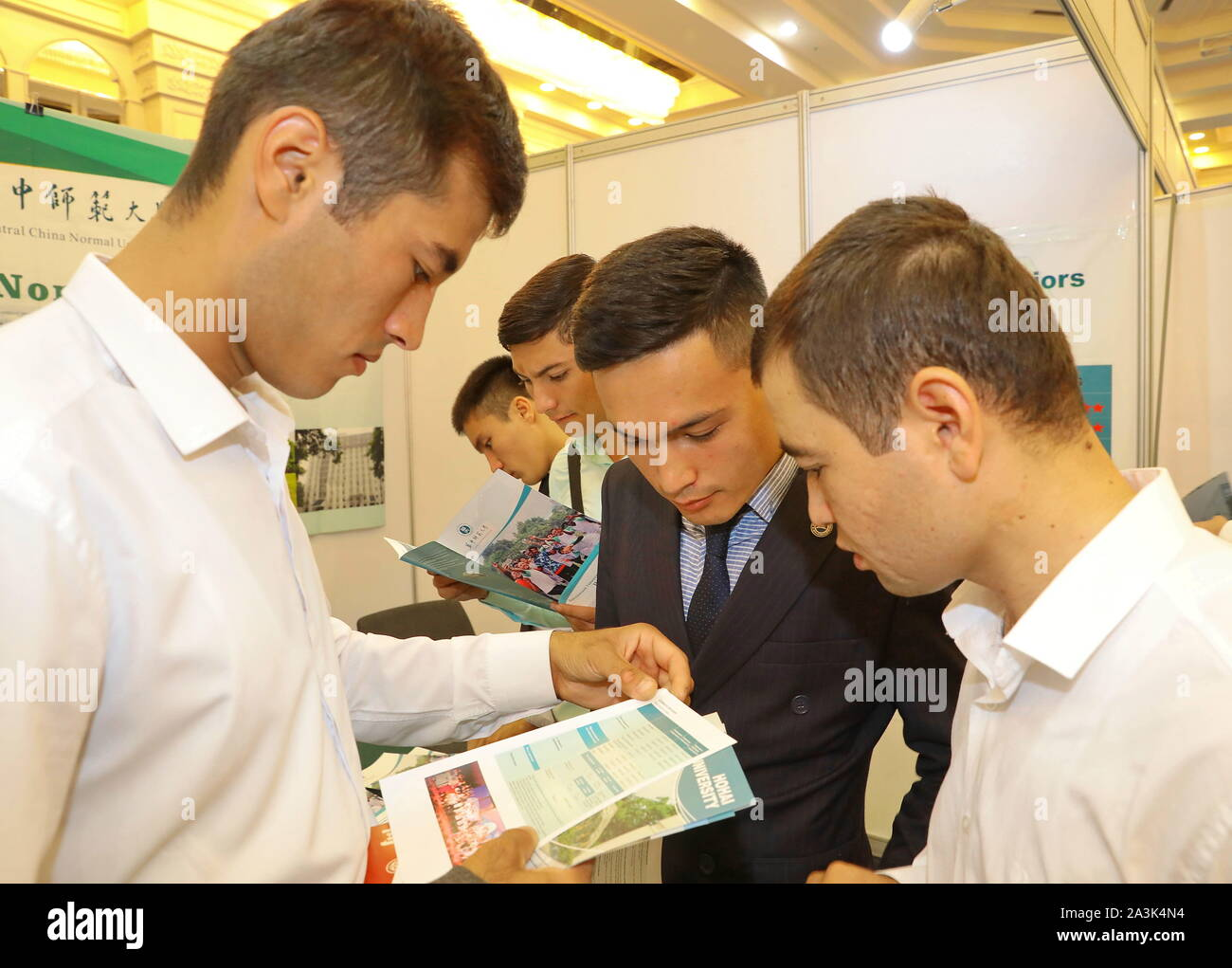 Tashkent, Uzbekistan. 8th Oct, 2019. Uzbek students read enrollment guides at an exhibition on higher education in China, in Tashkent, Uzbekistan, Oct. 8, 2019. An exhibition on higher education in China opened here Tuesday to familiarize Uzbeks with opportunities to study abroad in the East Asian country. Organizers said 30 leading higher educational institutions of China were presented at the event. Credit: Zafar Khalilov/Xinhua/Alamy Live News Stock Photo