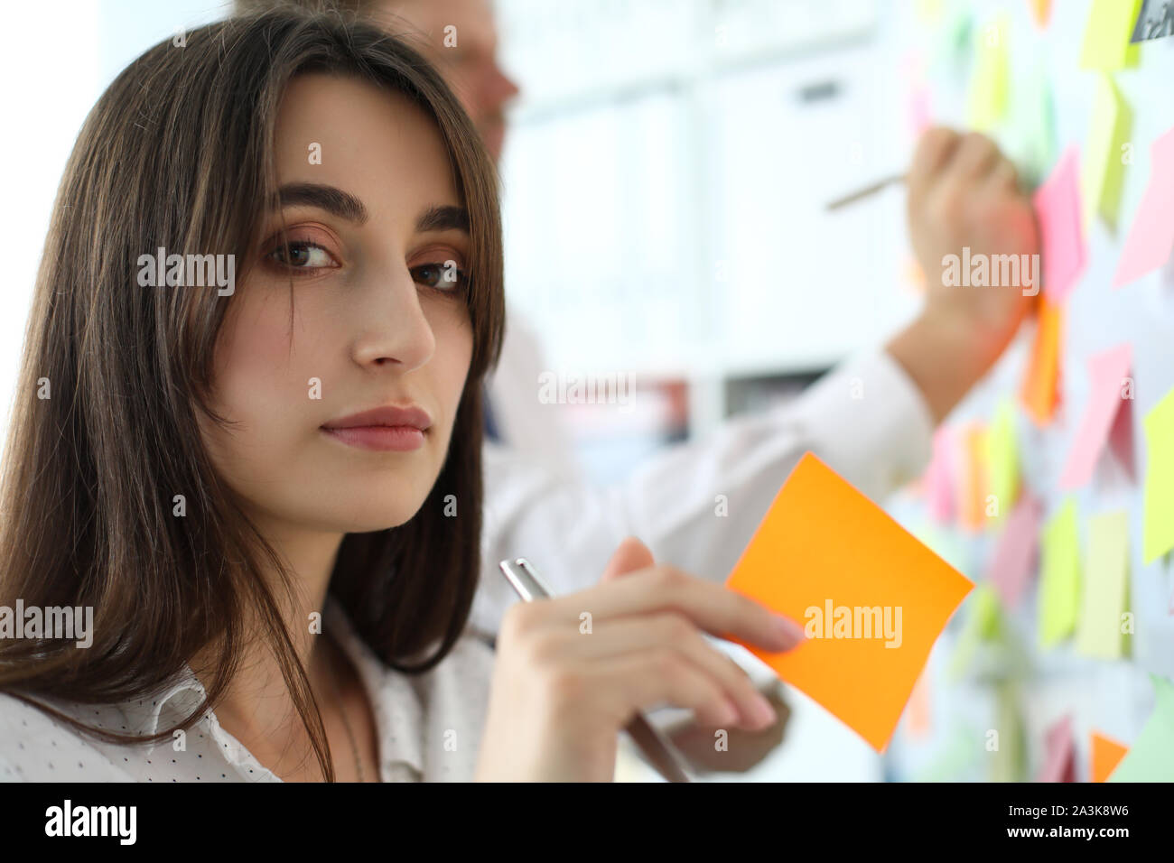 Pretty female office worker holding sticky paper looking in camera Stock Photo