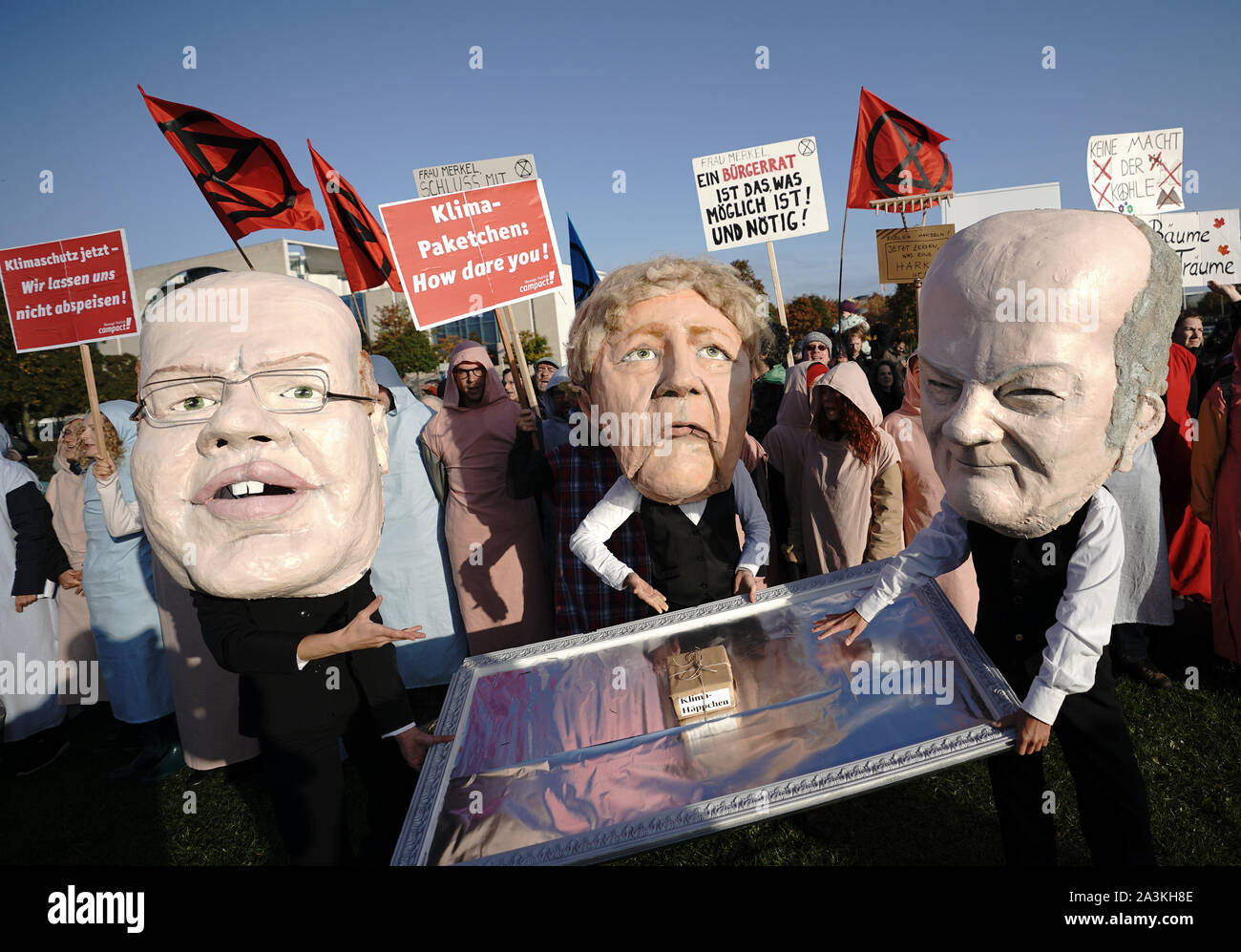 Berlin, Germany. 09th Oct, 2019. Campact activists are wearing masks, the Economics Minister Altmaier, Chancellor Merkel and Finance Minister Scholz are showing a small climate package on a silver platter during the Federal Cabinet meeting in front of the Chancellery. Credit: Michael Kappeler/dpa/Alamy Live News Stock Photo