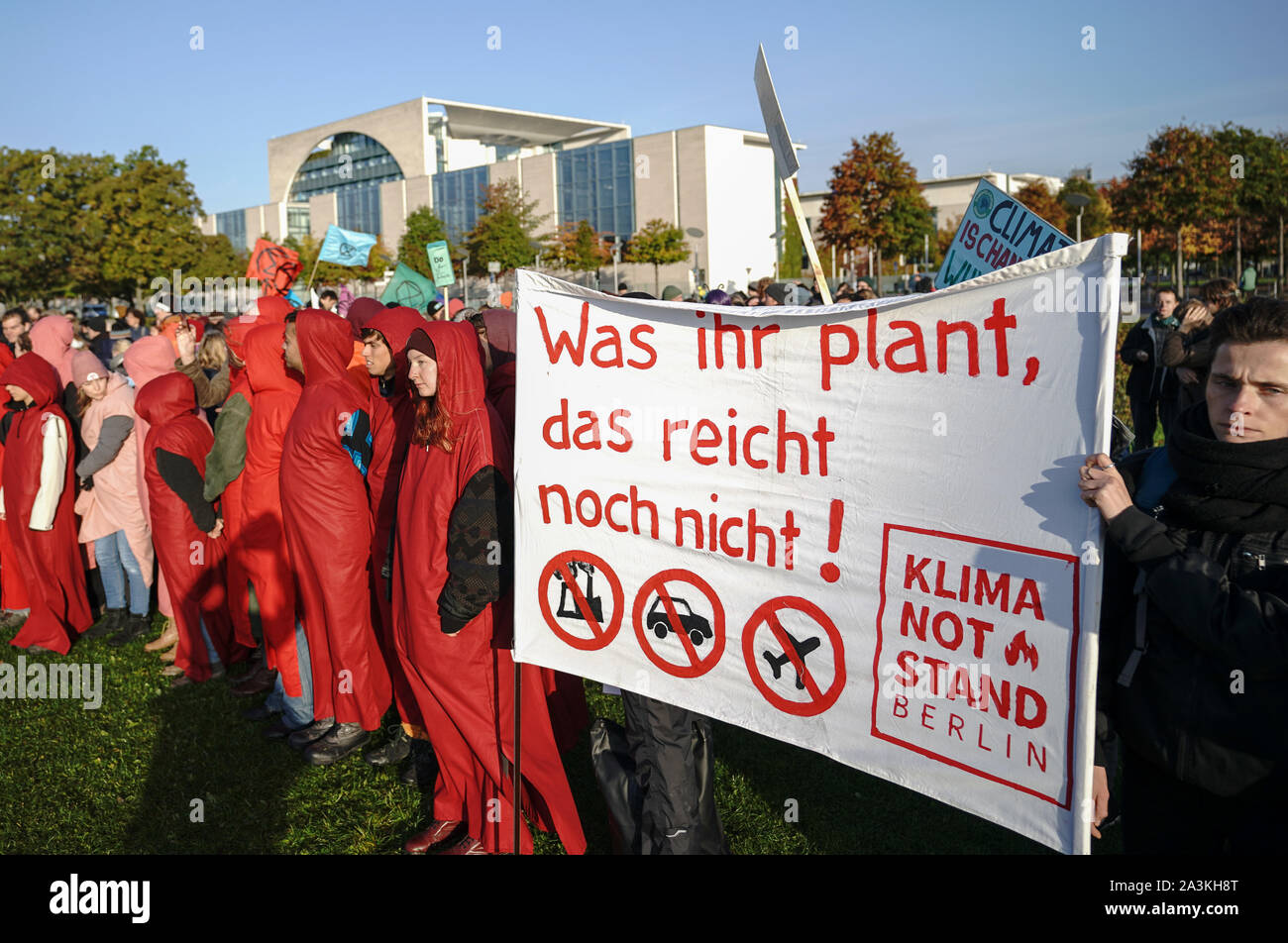 """Berlin, Germany. 09th Oct, 2019. Activists from Campact and other environmental movements stand in front of the Chancellor's Office with a banner saying """"What you are planning, that's not enough"""" during the Federal Cabinet meeting. Credit: Michael Kappeler/dpa/Alamy Live News Stock Photo"""