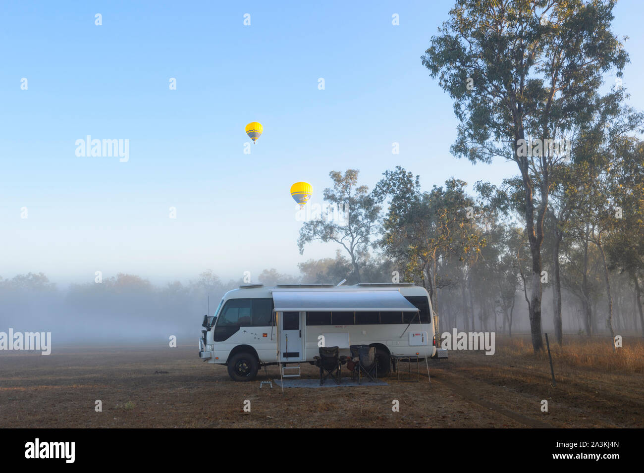 A Toyota Coaster motorhome camped at sunrise in the bush with yellow hot air balloons flying overhead, Mareeba, Queensland, QLD, Australia Stock Photo