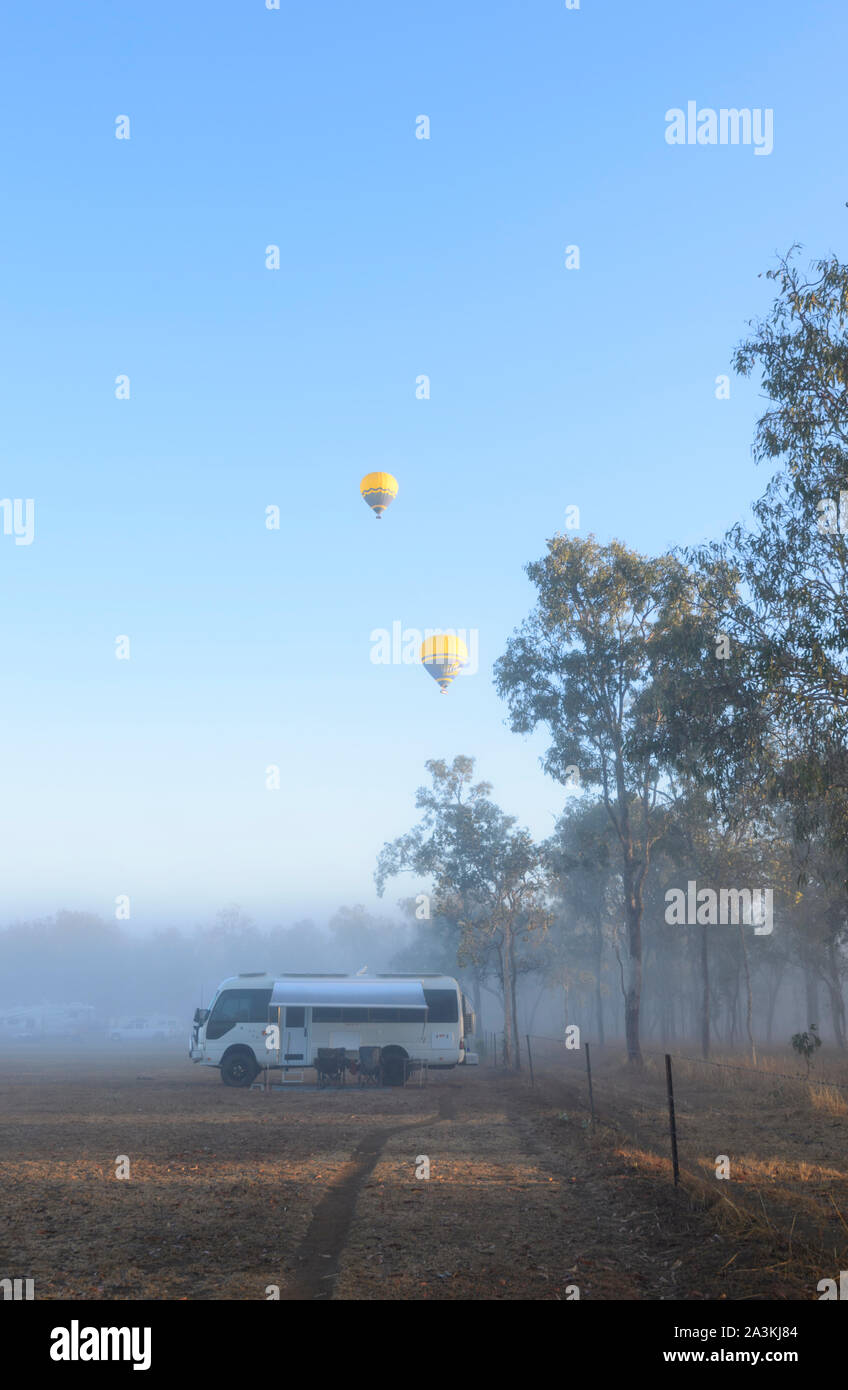 Vertical view of a Toyota Coaster motorhome camped at sunrise in the bush, with yellow hot air balloons flying overhead, Mareeba, Queensland, QLD, Aus Stock Photo