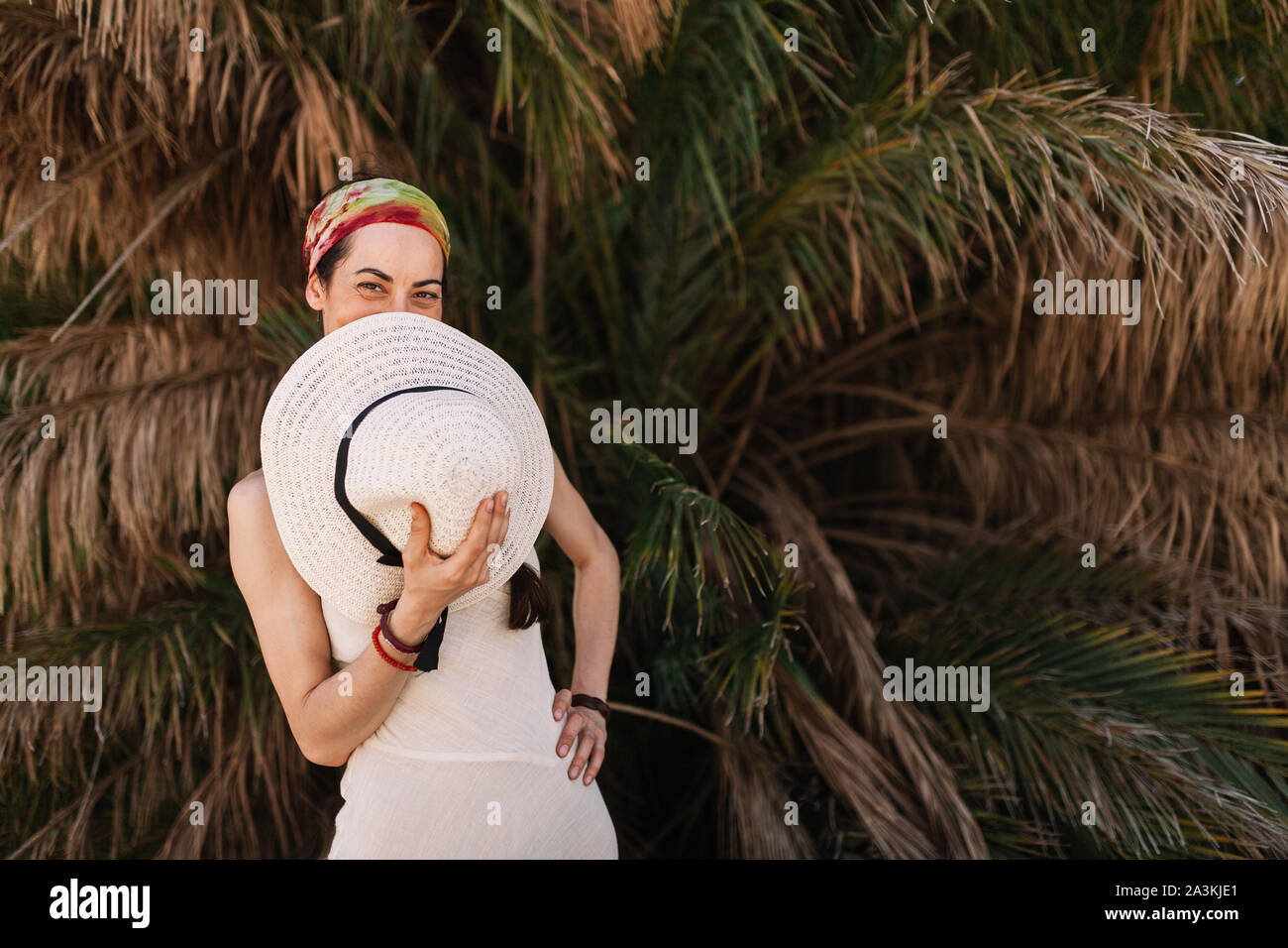 Young woman dressed in a white dress covers his mouth with hat standing close to palm tree Stock Photo