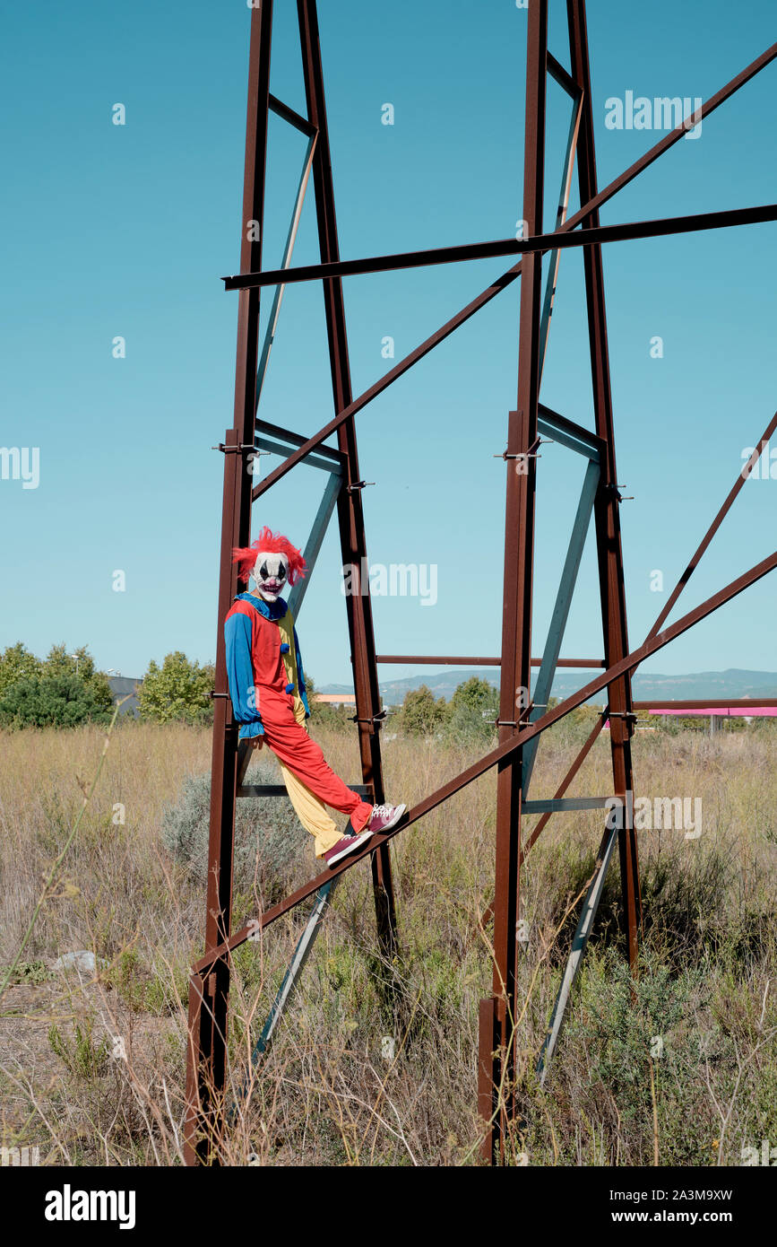 a scary clown wearing a colorful yellow, red and blue costume outdoors, hanging from the rusty structure of an abandoned billboard Stock Photo