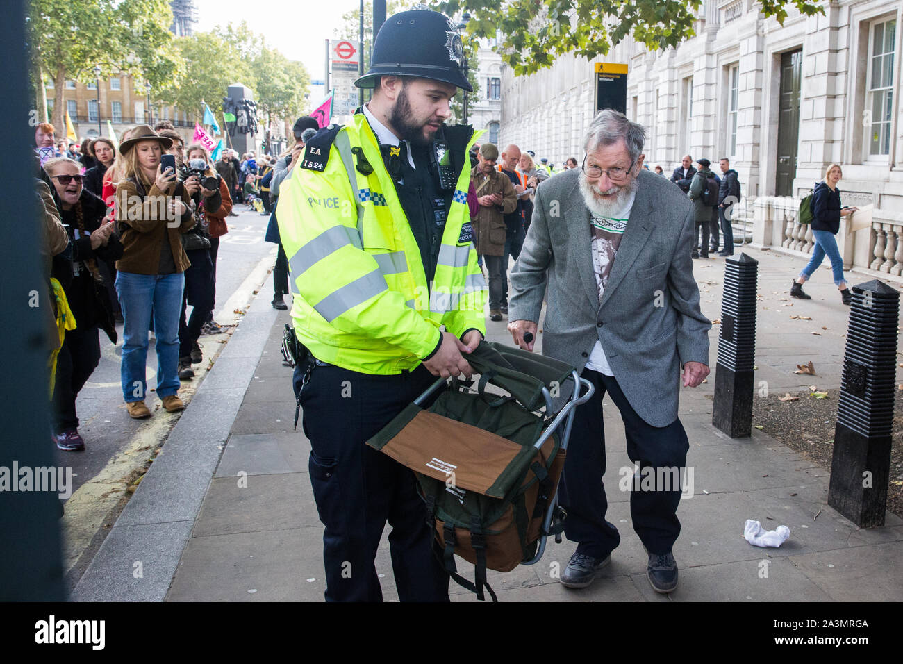 London, UK. 9 October, 2019. John Lynes, a 91-year-old climate activist from Extinction Rebellion is arrested by police officers using Section 14 of the Public Order Act 1986 after blocking Whitehall on the third day of International Rebellion protests to demand a government declaration of a climate and ecological emergency, a commitment to halting biodiversity loss and net zero carbon emissions by 2025 and for the government to create and be led by the decisions of a Citizens' Assembly on climate and ecological justice. Credit: Mark Kerrison/Alamy Live News Stock Photo