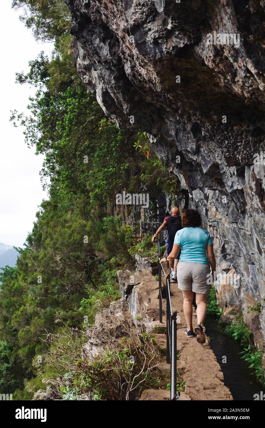 People walking on a narrow path on the edge of the rock during Levada do Caldeirao Verde Trail. Rocks and green trees. Dangerous hiking, trekking. Portuguese tourist attraction. Stock Photo