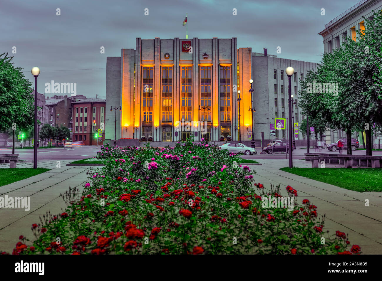 A government building illuminated at night and flowers in a park in St. Petersburg, Russia. Stock Photo