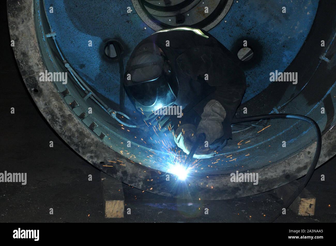 Professional welder welds an industrial tank in a workshop. Stock Photo