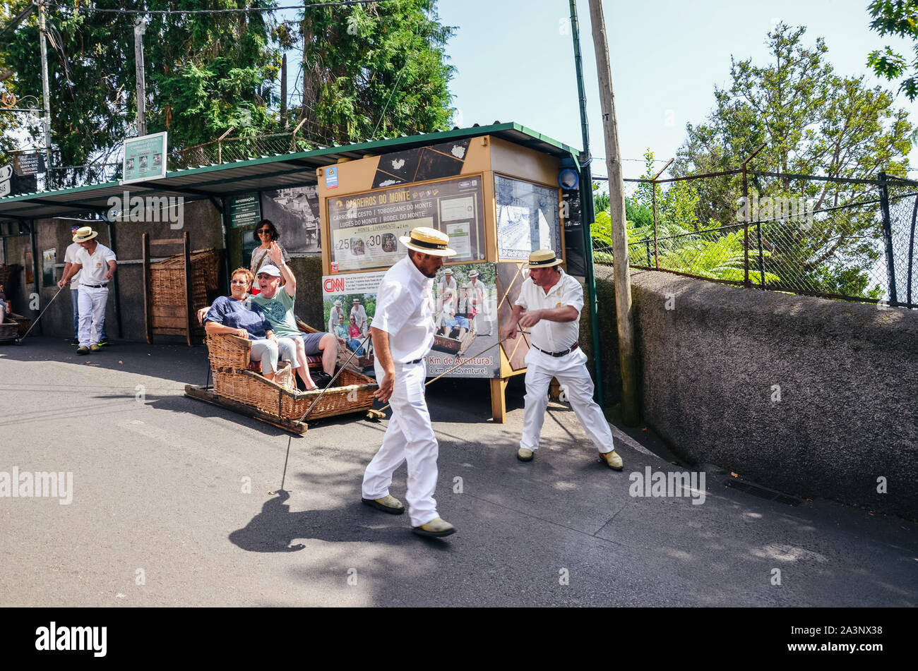 Monte, Madeira, Portugal - Sep 14, 2019: Wicker Basket Sledges drivers, Carreiros do Monte, driving tourists downhill. Traditional mean of transport, now a tourist attraction. Typical straw hats. Stock Photo