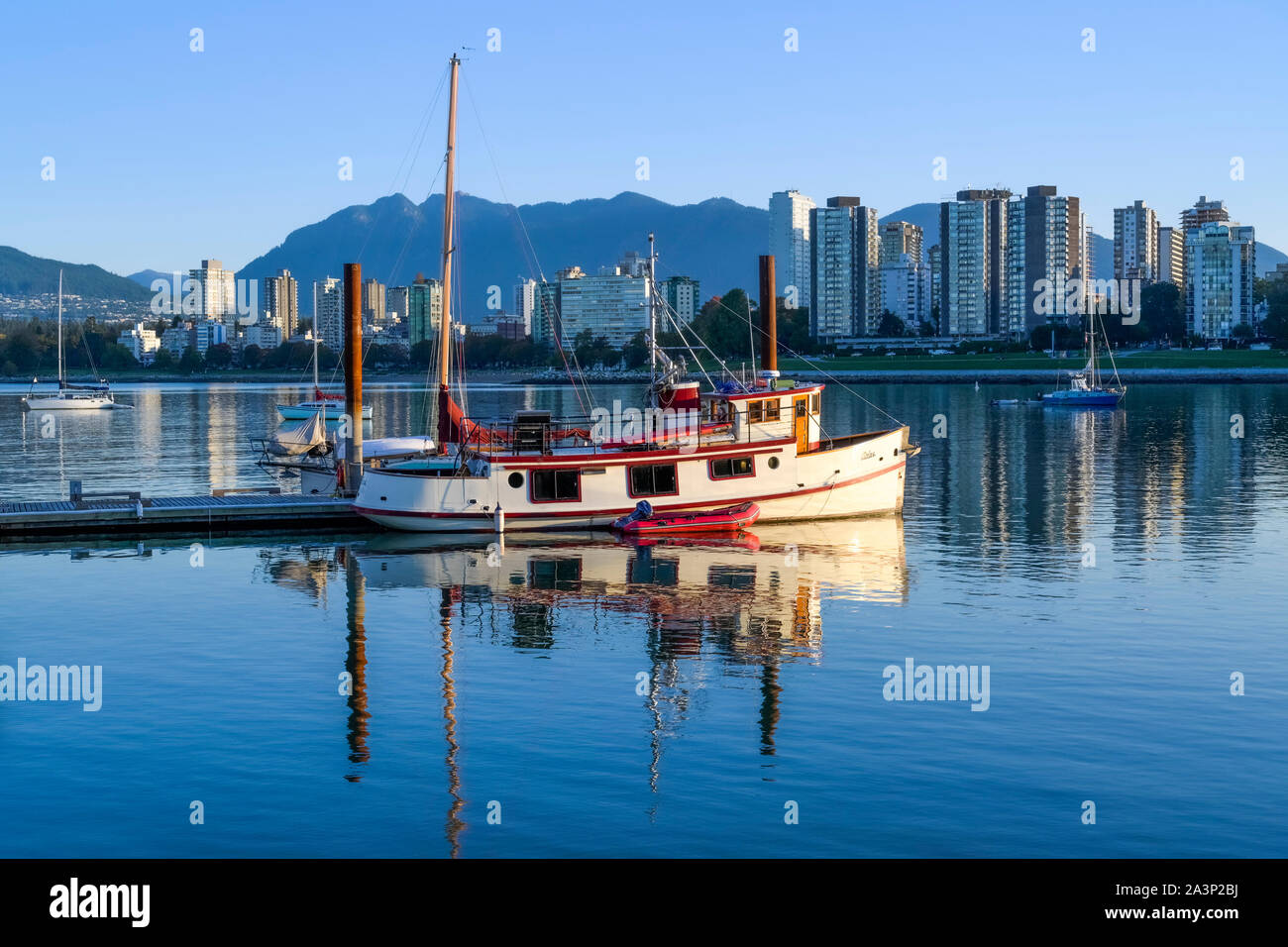 Heritage wooden boat, and West End from Elsje Point,  Vancouver, British Columbia, Canada Stock Photo