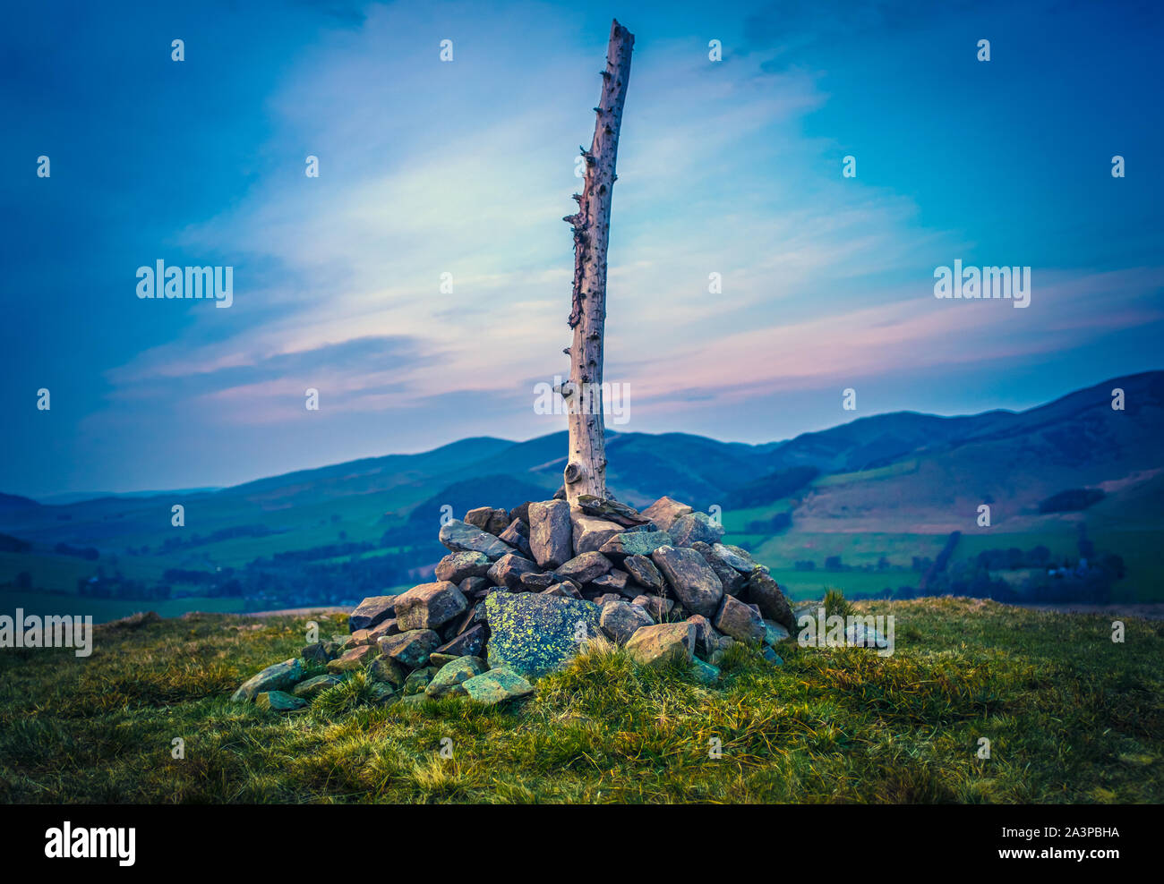 Scottish Hilltop With Cairn And Wooden Post At Sunset Stock Photo