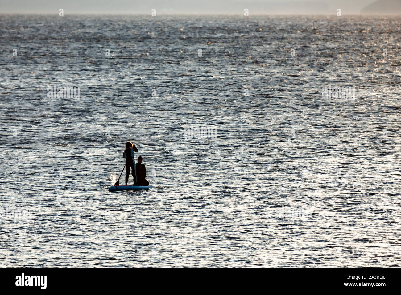 Couple paddleboarding off Llanddona beach, Anglesey, North Wales Stock Photo