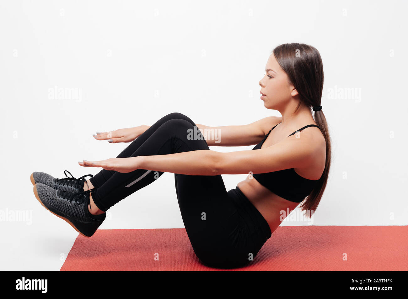 Side view of focused young lady in black sportswear performing sit up exercise for abs on red mat during fitness training against white background Stock Photo