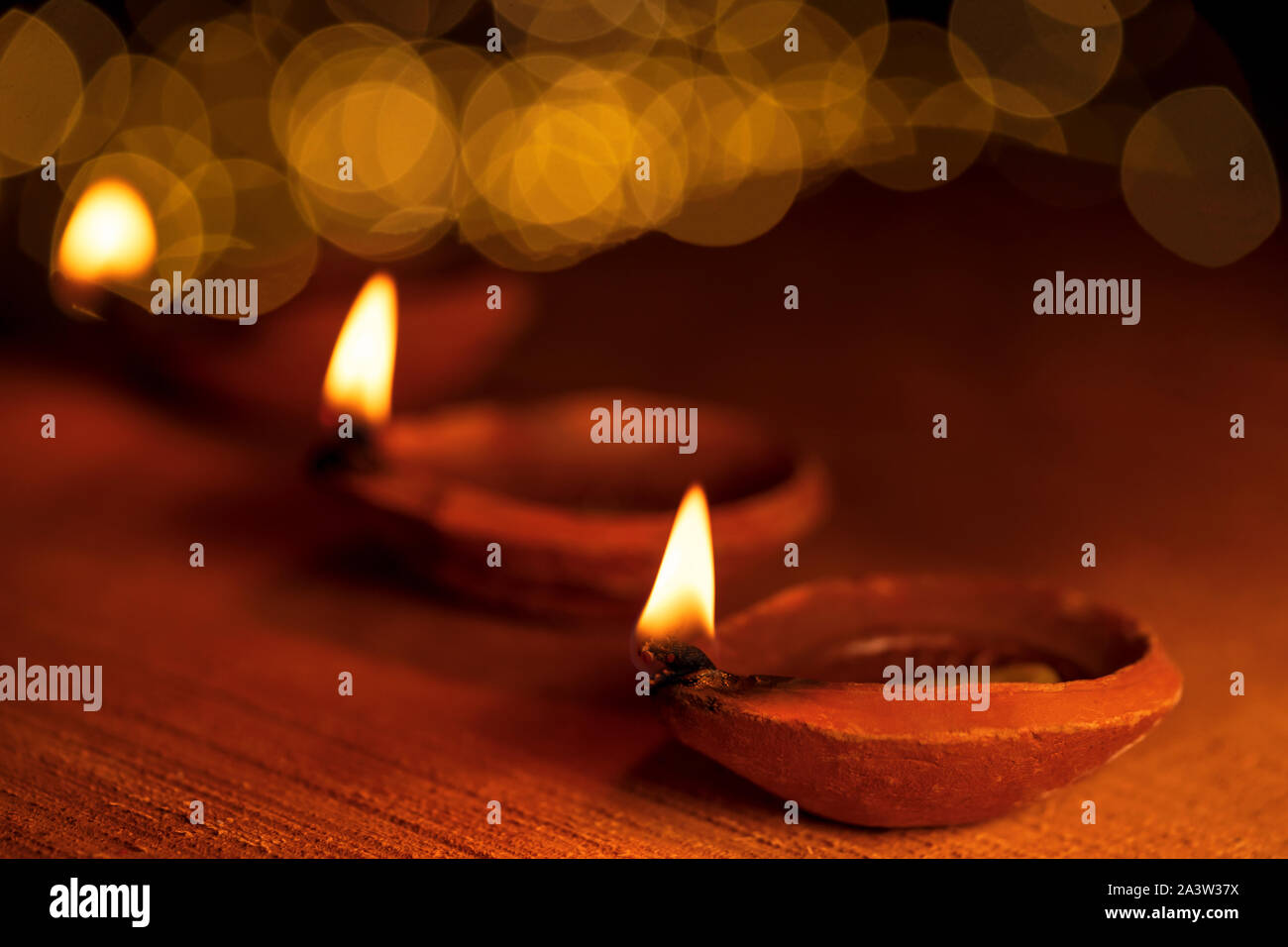 Happy Diwali background image of burning lit diya clay oil lamps with bokeh lights in the backround. Concept for Indian Hindu religious, tradition. Stock Photo