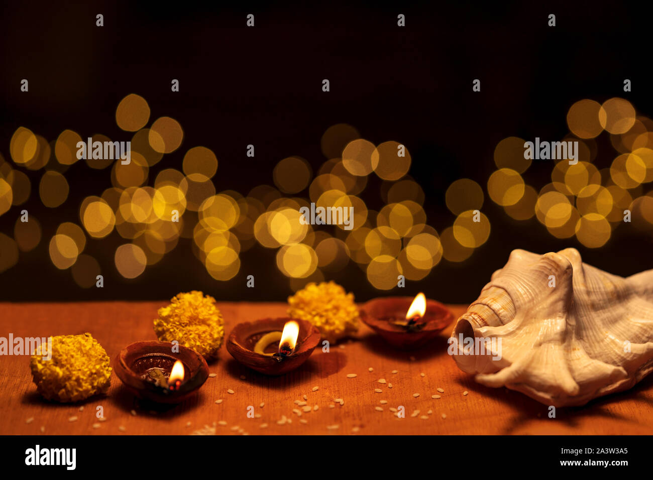 Diwali diya clay lamps decorated with flowers and shankha burning or glowing on a wooden background isolated in black with bokeh lights and copy space Stock Photo