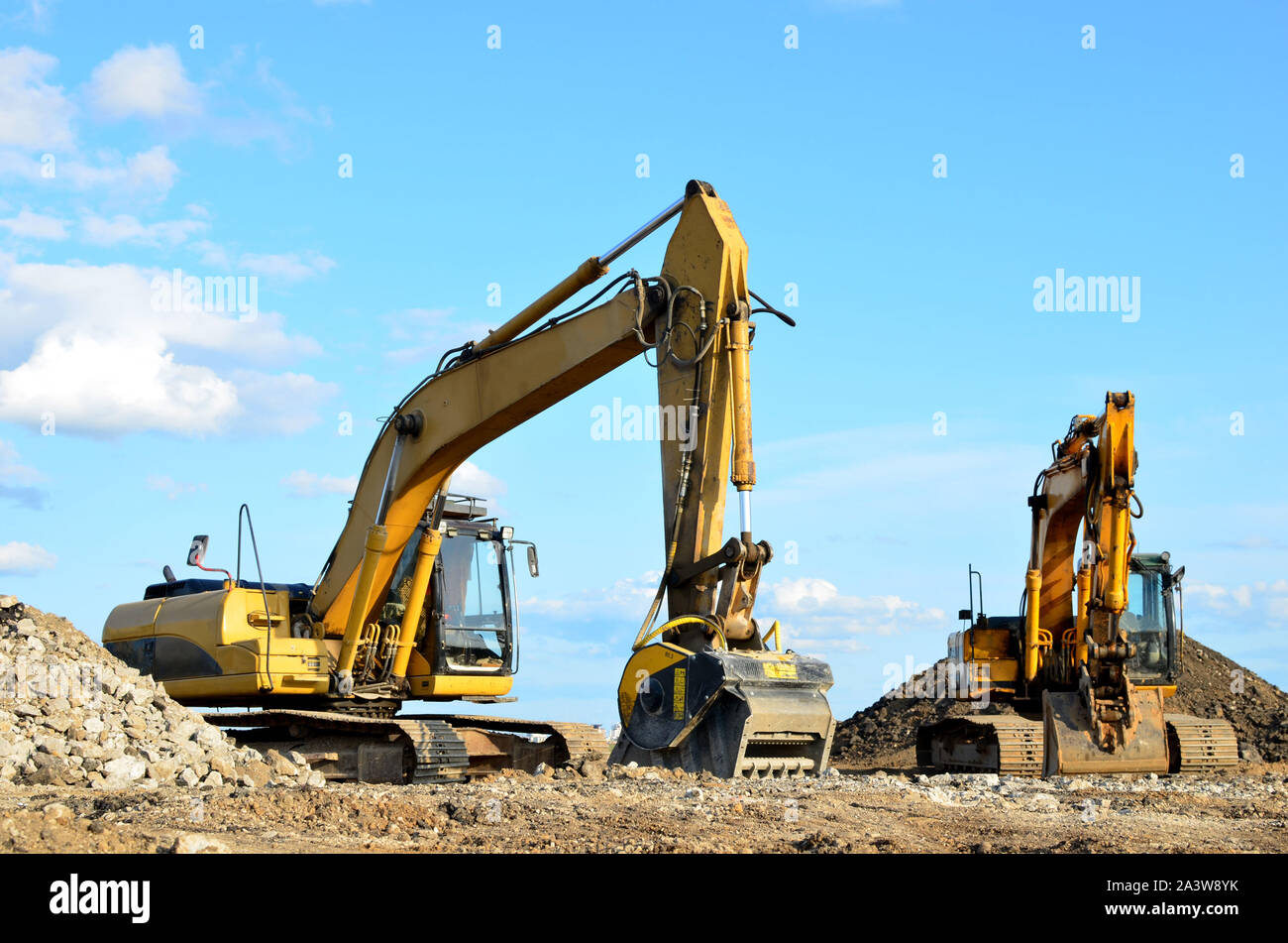 Two yellow excavators at a construction site. Excavator with crusher bucket for crushing concrete. Construction waste recycling for construction mix. Stock Photo