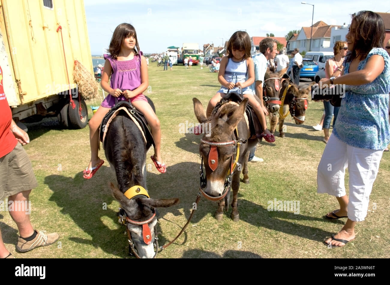 Two girls on Donkeys at a fair Stock Photo